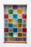 在白色墙壁的五颜六色的玻璃窗块 图库摄影