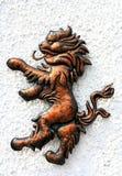 在白色墙壁的狮子古铜色形象 免版税库存照片