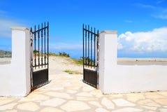 在白色墙壁的被打开的铁门有蓝天的 免版税库存图片