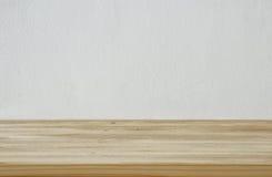 在白色墙壁纹理背景前面的空的桌 免版税图库摄影