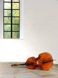 在白色墙壁附近的低音提琴在乌曼 图库摄影