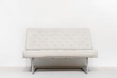 在白色墙壁附近的白色沙发在内部 简单派现代设计 库存图片