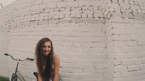 在白色墙壁,减速火箭的颜色射击附近的微笑的害羞的女孩 摆在bycicle倾斜的墙壁附近的少妇 减速火箭的颜色 股票视频