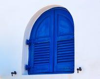在白色墙壁,圣托里尼,希腊上的著名被环绕的蓝色木窗口 免版税图库摄影