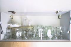 在白色壁橱的另外玻璃器皿在架子 银行,水罐,玻璃,杯子 库存照片