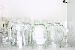 在白色壁橱的另外玻璃器皿在架子 银行,水罐,玻璃,杯子 免版税库存图片