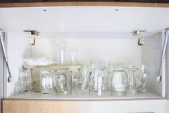 在白色壁橱的另外玻璃器皿在架子 银行,水罐,玻璃,杯子 库存图片