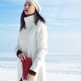 在白色外套的时兴的模型在冬天海附近 免版税库存图片