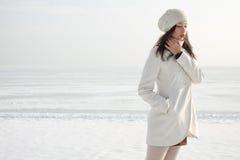 在白色外套的时兴的模型在冬天海附近 图库摄影