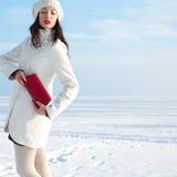 在白色外套的时兴的模型在冬天海附近 库存照片