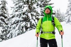 在白色多雪的森林走与远足的冬天远足者棍子和 免版税库存图片