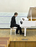 在白色大平台钢琴后的钢琴演奏家 免版税库存照片