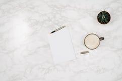 在白色大理石桌背景的空白的笔记本页 免版税库存照片