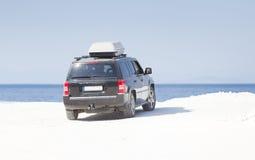 在白色大理石海岸的汽车 库存照片