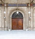 在白色大理石的木华丽门装饰了墙壁 免版税库存图片