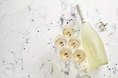 在白色大理石背景和瓶安置的香宾玻璃 库存图片