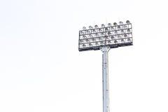 在白色天空背景的体育场泛光灯 免版税图库摄影