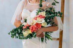 在白色婚礼礼服的婚礼花束在美丽的新娘的手上 库存图片