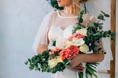 在白色婚礼礼服的婚礼花束在美丽的新娘的手上 库存照片