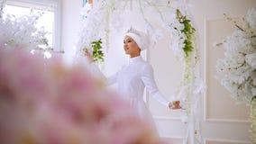 在白色婚礼礼服的美好的回教模型与摆在演播室的回教头饰 影视素材