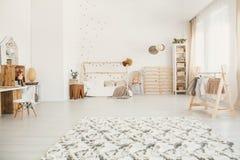 在白色孩子卧室内部的蓬松地毯与家型是 图库摄影
