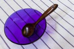 在白色安置的浅紫色的烹调玻璃碗的木匙子 免版税库存照片
