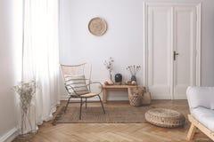 在白色客厅内部的窗口的纯粹白色帷幕与一个镶边的,亚麻制枕头的在一把现代藤椅 免版税库存照片