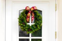 在白色家门的圣诞节花圈 库存图片