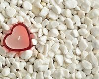 在白色小卵石显示的一个红色心脏形状蜡烛 免版税库存照片