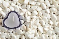 在白色小卵石显示的一个蓝色心脏形状蜡烛 免版税库存图片