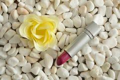 在白色小卵石显示的一支红色唇膏 库存图片