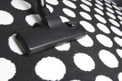 在白色小点地毯的吸尘器 免版税图库摄影