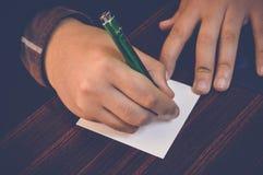 在白色小笔记的手文字 免版税库存图片