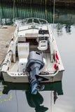 在白色小船的黑马达有加拿大旗子的 免版税库存照片
