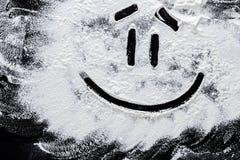 在白色小麦面粉的面带笑容在抽象黑背景 库存图片