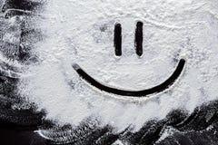 在白色小麦面粉的面带笑容在抽象黑背景 图库摄影
