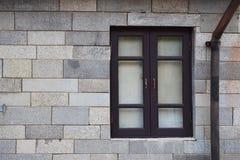 在白色岩石墙壁上的老黑窗口 库存图片