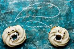 在白色巧克力的万圣夜油炸圈饼与牙和眼睛在蓝色 免版税库存照片