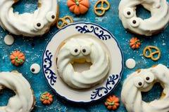 在白色巧克力的万圣夜油炸圈饼与眼睛 创造性的想法为 免版税库存照片