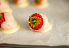 在白色巧克力盖的一个新鲜的草莓 图库摄影