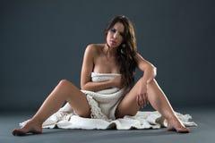 在白色布料盖的美丽的肉欲的裸体妇女 免版税图库摄影
