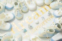 在白色布料背景的男婴蓝色毛线框架 欢迎新出生的阵雨党 梦想明天 - 顶视图 免版税库存图片