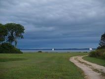 在白色帆船后的风雨如磐的天空 图库摄影