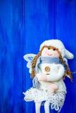 在白色帽子和灰色围巾的圣诞节天使 免版税库存照片