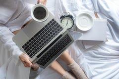 在白色床上的亚裔妇女 妇女读醒,并且工作在膝上型计算机和阅读书和饮用的咖啡在早晨放松moo 免版税库存图片