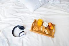 在白色床上的早晨早餐 盘子新月形面包咖啡奶蛋烘饼汁 免版税库存照片