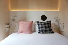 在白色床上的格子花呢披肩枕头 图库摄影