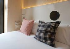 在白色床上的格子花呢披肩枕头 库存图片