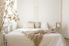 在白色床上的毯子与在最小的卧室内部的坐垫与植物和桌 免版税库存照片