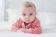 在白色床上的逗人喜爱的婴孩 图库摄影